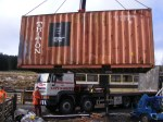 The brown container being lifted into place in it's new home in the compound.