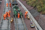 As the rails come off the train they are supported on rollers just above the sleepers to make the task of removing the rails from the train easier.