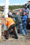 Tony and Baz helping Mike to align and lower the signal post down onto the mounting.