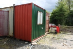 Work continues on the office container, with more primer applied.
