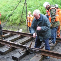 "After swinging the track panels into position Bill Blake places and tightens the ""golden bolt"" on the first track joint watched by WRHA volunteers Iain MacIntosh, Alan Anderson, John Moore Scott, Andy Laing & Ian Cairns. July 2005."
